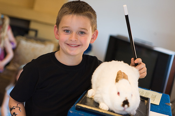 Magic Glen - Boy holding a magic wand and a rabbit on the table